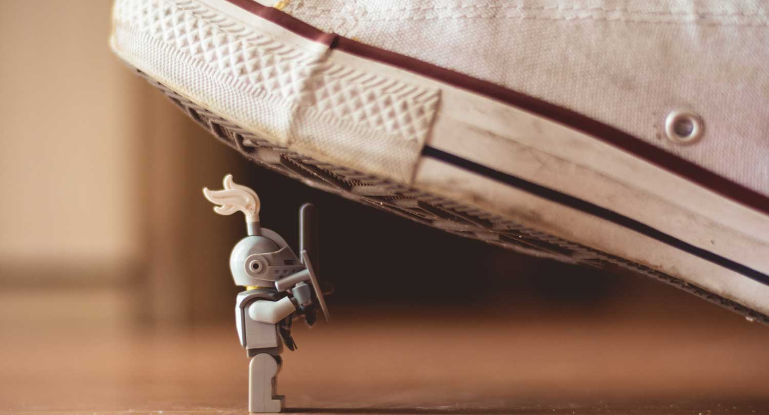 Lego figure of a knight underneath canvas shoe